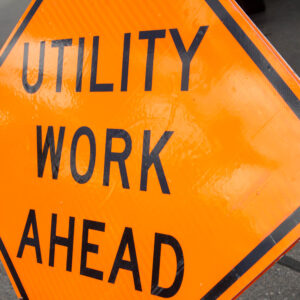 Tilted orange utility work ahead sign